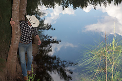 cowboy by a still lake in the woods