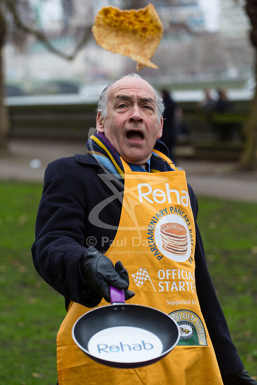 MPs and members of the House of Lords compete in the annual Rehab pancake race, a relay of eleven laps in Victoria Tower Gardens adjacent to the Houses of Parliament in London. The race is held every year on Shrove Tuesday and was won by the Media team. PICTURED: Official starter.  London, February 13 2018.