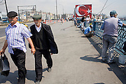 08 AUGUST 2007 -- ISTANBUL, TURKEY: Men walk across the Galata Bridge, which spans the Golden Horn between the European parts of Istanbul, Turkey. Istanbul, a city of about 14 million people, and the largest city in Turkey, straddles the Bosphorus Straits between Europe and Asia. It is one of the oldest cities in the world. It was once the center of the Eastern Roman Empire and was called Constantinople, named after the Roman Emperor Constantine. In 1453, Mehmet the Conqueror, Sultan of the Ottoman Empire, captured the city and made it the center of the Ottoman Turkish Empire until World War I. After the war, the Ottoman Empire was dissolved and modern Turkey created. The capitol was moved to Ankara but Istanbul (formerly Constantinople) has remained the largest, most diverse city in Turkey.    Photo by Jack Kurtz