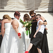Liberty Manos accepts her bouquet of flowers from nephew Elijah Maxwell, before entering the Supreme Court in order to descend the steps to cheers from friends and family, on June 21, 2013. Twenty-five gay couples traveled to Washington on the C-Bus of Love to get married en masse the week before decisions are expected to be made on the Defense of Marriage Act (DOMA) and Proposition 8. John Boal photography