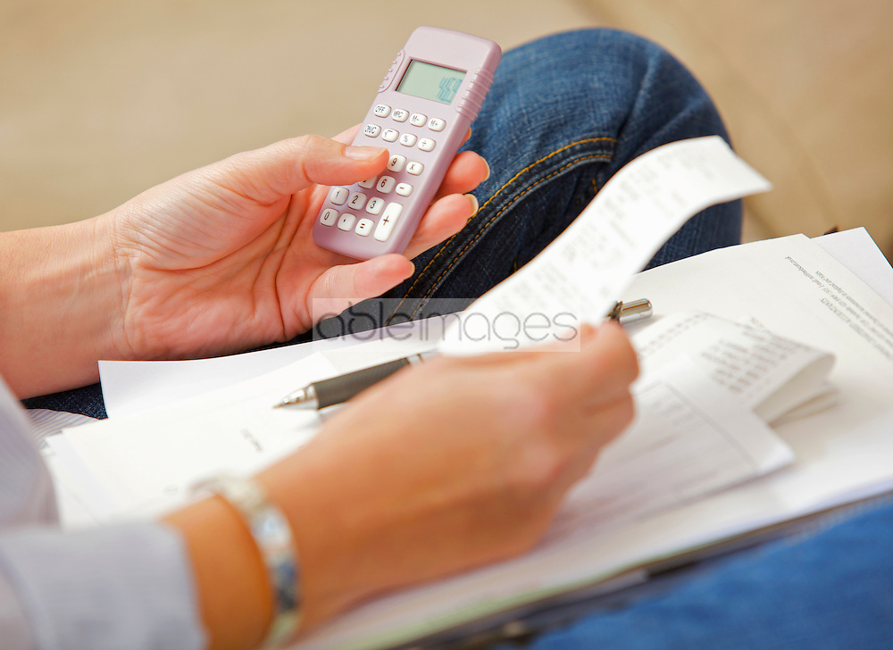 Woman's Hands Holding Receipt and Calculator