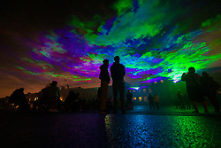 © Licensed to London News Pictures. 10/09/2021. London, UK. People watch a laser and smoke art installation entitled 'Borealis' by Swiss artists Dan Acher as it illuminates the night sky over Royal Artillery Barracks at Woolwich, south east London. This spectacular installation is inspired by the experience of the Northern Lights, and shines over locations in the Royal Borough of Greenwich during this year's Greenwich + Docklands International Festival.Photo credit: Peter Macdiarmid/LNP