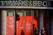 Sale reductions at a branch of UK retailer Marks & Spencer, on Bishopsgate in the City of London. With their own shadows two women consumers walk past smiling, near a banner announcing the new post-Christmas winter sale offering up to 60% reductions on clothing. Marks & Spencer has over the last 129 years grown from a single market stall to become an international multi-channel retailer, now operating in over 50 territories worldwide and employing almost 82,000 people.
