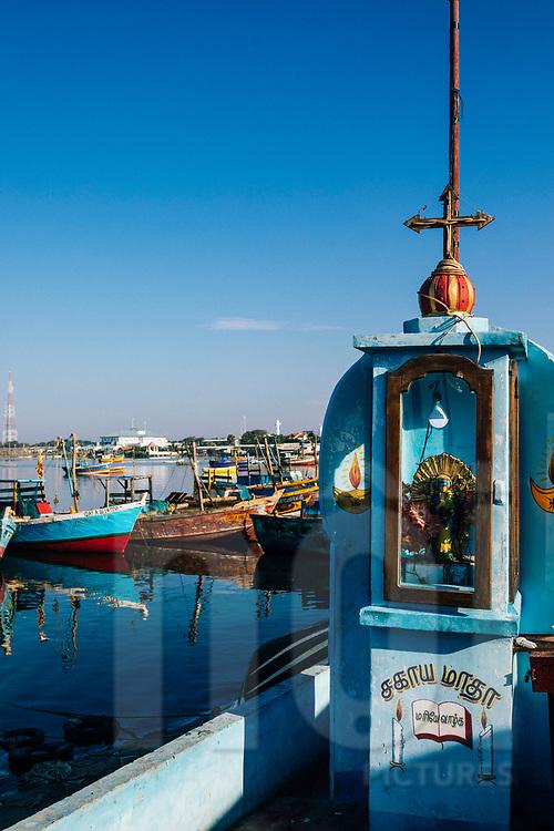 A saint statue guards over boats at a small fishing village, Jaffna Peninsula, Sri Lanka, Asia
