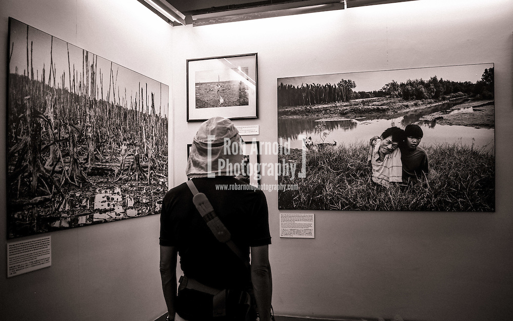 One of the most hard-hitting stories of the exhibition on the effects of Agent Orange in the War Remnants Museum in Ho Chi Minh City. Nguyen Can Hung was originally photographed in Ca Mau (left), by the Japanese Photojournalist Bunyo Ishikawa, standing in 1976 amongst trees devastated by the herbicide chemical Dioxin, sprayed by the US military. The photo on the right is Hung (left) and his elder son Hao (right) in 2007, sitting in front of the spot (now a shrimp farm) where he was originally photographed as a seven year old boy. Suffering from cerebral palsy and parkinson's disease, he was left almost speechless from the chemical poisoning. He died in 2008 from his illnesses.