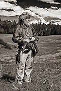 Mountain Man and his trapping and hunting gear and the distant Grand Teton Mountain Range.