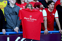 An Arsenal fan in the stands holds up a t-shirt honouring outgoing manager Arsene Wenger