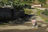 Cleaning the village road. Lesser Lake Prespa, Lake Prespa National Park, Albania June 2009