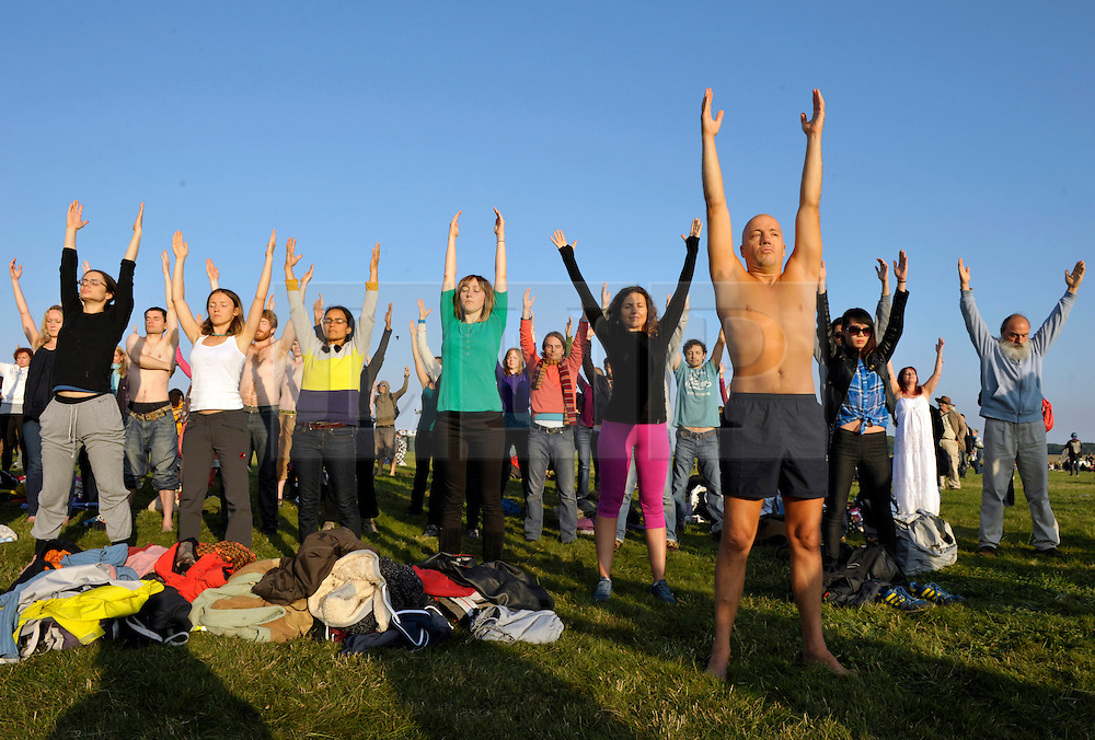 © Licensed to London News Pictures. 21/06/2014; Amesbury, WIltshire, UK.  An open air yoga group practice as thousands of people welcome the solstice on the longest day at Stonehenge.<br /> Photo credit: Simon Chapman/LNP