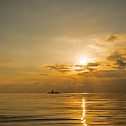 """A small wooden Bunka going out fishing in the sunset.<br /> <br /> The SARANGANS showcase enormous cultural diversity of Blaan, Tboli, Tagakaolo, Kalagan, Manobo, Ubo, Muslim tribes and Christian settlers. Hospitable and fun-loving """"Sarangans"""" (people of Sarangani) adhere to a unified direction for development.<br /> Muslim consists of 7 groups; the Lumads, 17; and the migrant settlers, at least 20. The Blaans characterize the largest minority and are distributed in the municipalities of Malapatan, Glan, Alabel, Maasim, and Malungon. A bulk of this tribe is found in Malapatan constituting 37% of the municipal household population.<br /> The Maguindanaos are settled in the municipalities of Malapatan, Maitum, and Maasim; Tbolis reside mostly in Maitum, Kiamba, and Maasim while Tagakaolos subsist entirely in Malungon.<br /> Cebuano settlers are found in Glan and Alabel; Ilonggos are situated in Malungon while the Ilocanos live mostly in Kiamba and Maitum.<br /> Thus, Sarangani's mixed population of Cebuano-speaking Blaans and Muslims in the east coast, Ilocano-speaking Tbolis, Manobos and Muslims in the west coast, and Ilonggo-speaking Blaans and Kaolos in the north uplands, is unique and in harmony."""