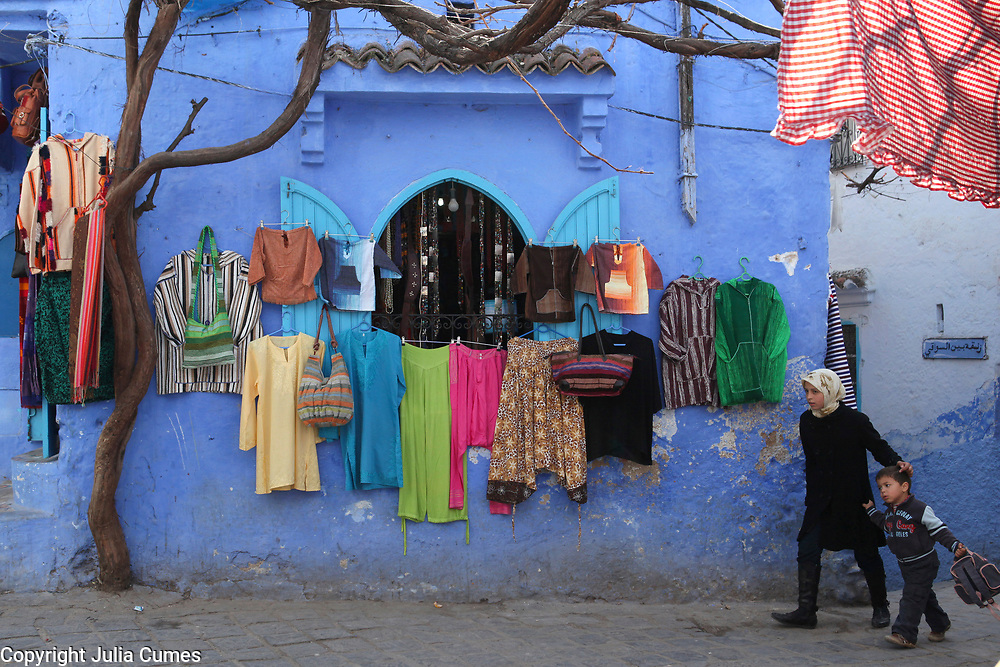 """A girl walks her brother home from school past a display of colorful clothes, offset by the striking blue walls in Chefchaouen, Morocco, whose """"medina"""" (old city) is famous for its blue buildings."""