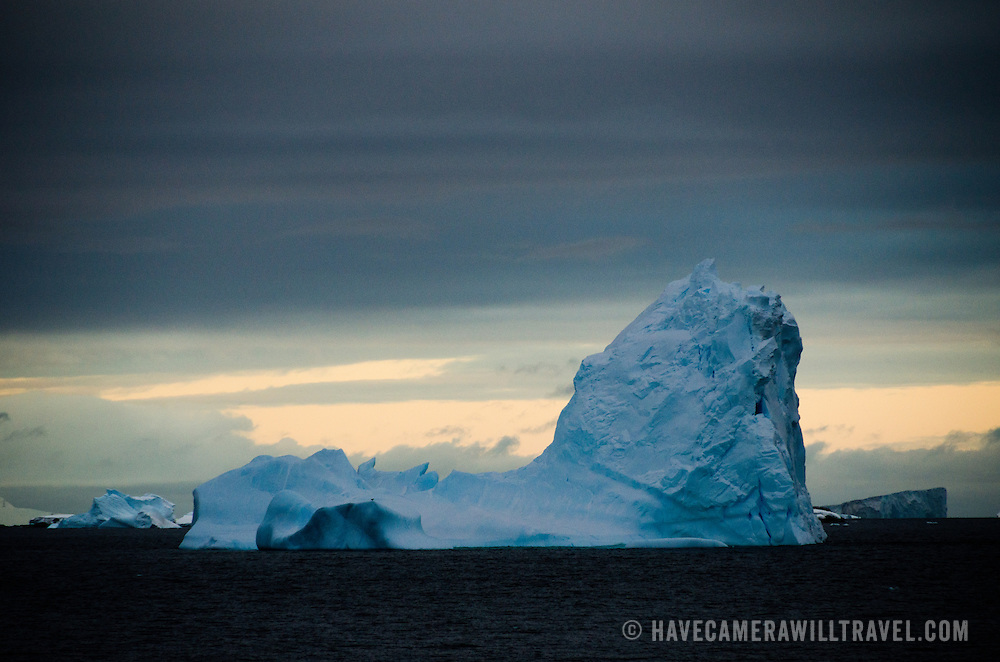 A blue iceberg floats in the water during the Antarctic twilight near Trinity Island, Antarctica.
