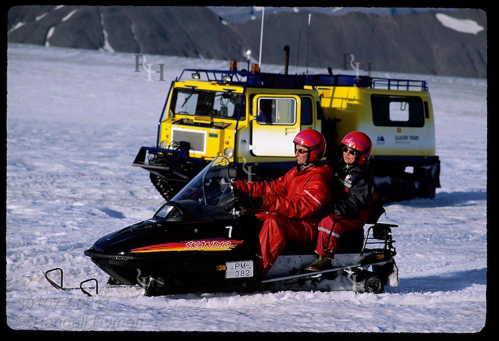 Couple races past snowbus on a snowmobile atop Vatnajokull glacier during a two-hour Glacier Tours trip; southeast Iceland.