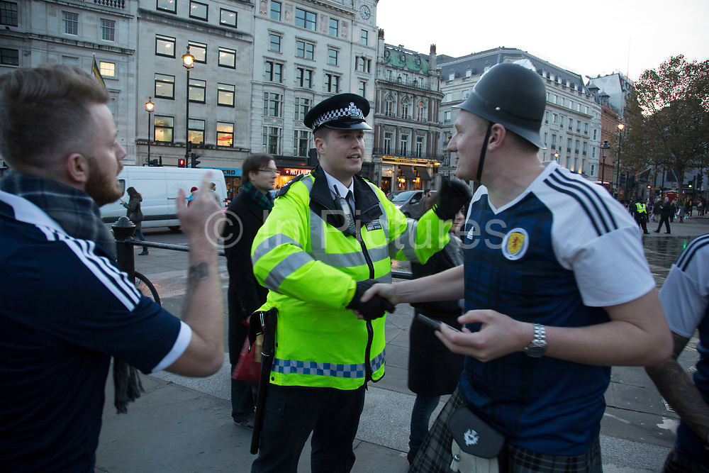 Scotland fans joke with a police officer in joyous mood drinking and singing together in Trafalgar Square ahead of their football match, England vs Scotland, World Cup Qualifiers Group stage on 11th November 2016 in London, United Kingdom. The Home International rivalry between their respective national teams is the oldest international fixture in the world, first played in 1872.