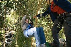 Chile, Lake Country: Canopying or ziplining adventure sport of sliding on a steel line through the canopy of the trees near Peulla..Photo #: ch622-33473..Photo copyright Lee Foster www.fostertravel.com, lee@fostertravel.com, 510-549-2202.