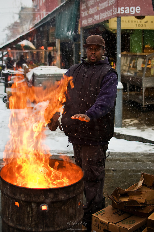 A worker, early on a cold winter's morning in Philly's Italian Market, keeps his hands warm by the fire used to discard cardboard and wood pallets.