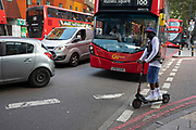 Public transport TFL buses and an e-scooter at Elephant and Castle in London, UK. The area is now subject to a master-planned redevelopment budgeted at £1.5 billion. A Development Framework was approved by Southwark Council in 2004. It covers 170 acres and envisages restoring the Elephant to the role of major urban hub for inner South London.