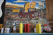 Condiments sit neatly arranged for patrons below corn dog mural at Cozy Dog Inn, a famous Route 66 eatery featuring hot dogs breaded with deep-fried corn meal; Springfield, Illinois.