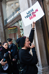 London, December 6th 2014. Tens of thousands throng the streets of London as shoppers take advantages of ongoing deals and discounts offered by retailers in the run-up to Christmas. PICTURED: Animal rights protesters from a London Vegans' group demonstrate outside Benetton's Oxford Circus store, against the use of rabbit fur on some of their garments.