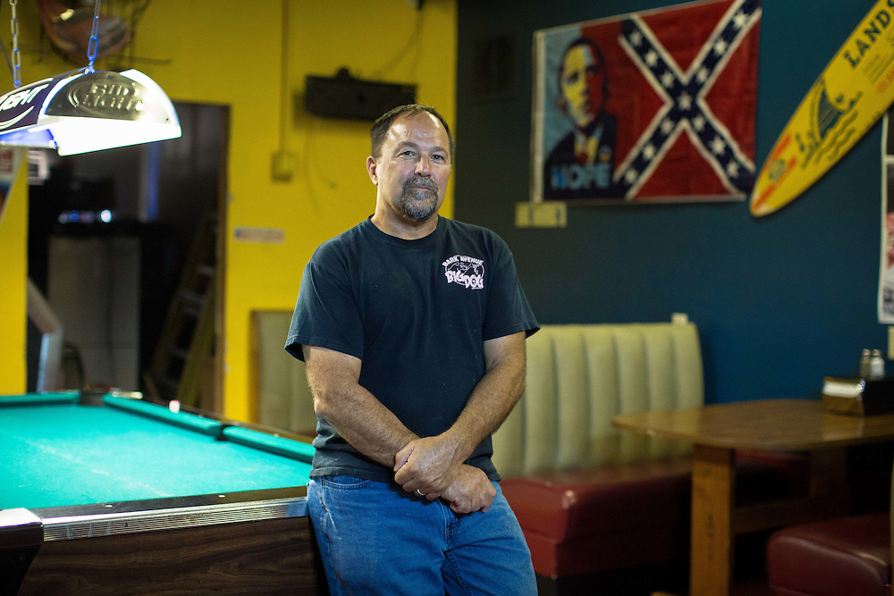"""Portrait of Patrick Lanzo, owner of Georgia Peach Oyster Bar in Paulding County, Ga. Lanzo, who says he is on the FBI's Terrorist Watchlist for many of the controversial things he has done, including placing a sign out front of his business that read """"Obama. A vision of a dream. James Earl Ray."""" He is photographed inside the establishment on Thursday, July 2, 2015. Shot for a story about changes occurring in the South following a heightened national awareness and sensitivity concerning the Confederate battle flag. Photo by Kevin Liles for The New York Times"""