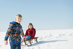 Boy pulling girl on sledge, Bavaria, Germany