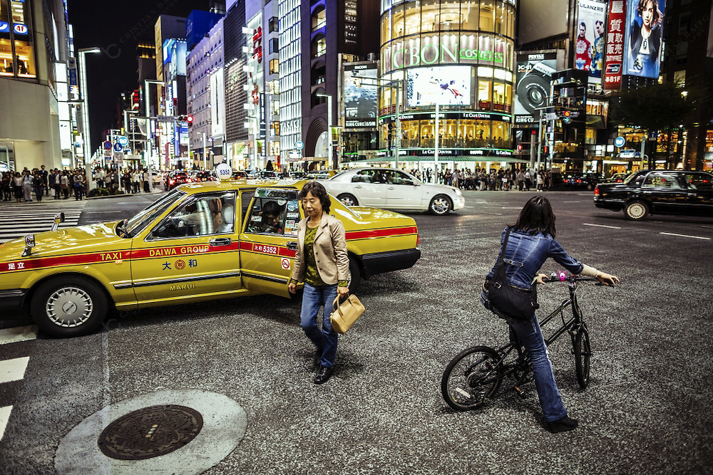 Ginza district at night Tokyo JapanTokyo, Ginza - October 13, 2012: Traffic and people in Ginza Tokyo Japan. Ginza is a district of Chuo Tokyo known because of the upmarket stores, boutiques,night clubs, cafes and restaurants. It is the most expensive area in the city and nearly all the international luxury brands are are represented here.