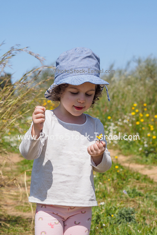 Young toddler girl playing outdoors, alone in nature