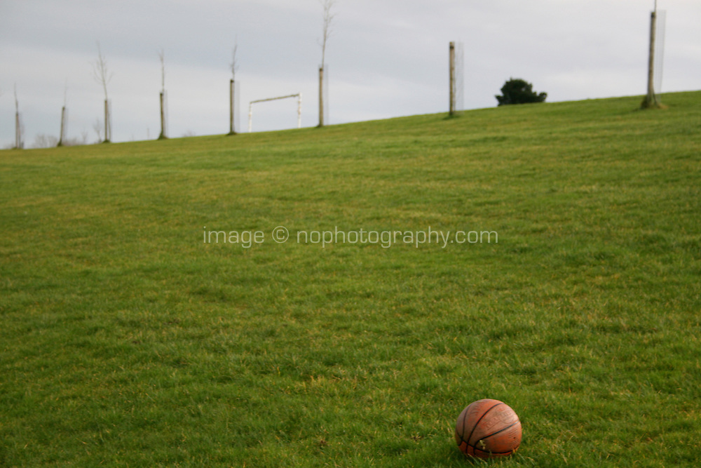 Abandoned basketball in field at a park in Dublin Ireland