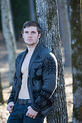 sexy man with an open button down sweater leaning against a tree