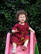 Toddler girl plays outdoors in her garden