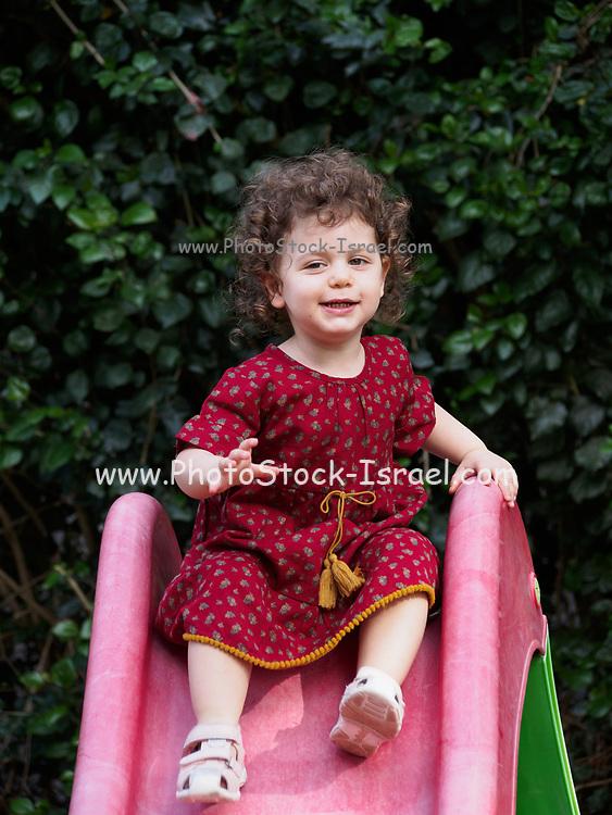 Toddler girl plays outdoors in her garden
