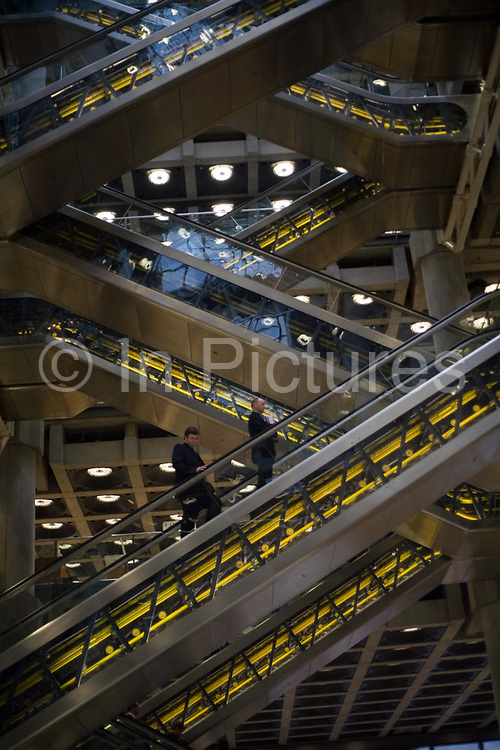 Escalators carry staff and brokers through the Lloyds Building in London. The modern building was designed by Sir Richard Rogers at Number One Lime Street in a Post-Modernist style. The trading floor at Lloyds is the world's leading insurance market where It serves as a meeting place where multiple financial backers or 'members', whether individuals (traditionally known as 'Names' or corporations, come together to pool and spread risk.