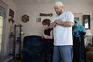 """Abdul-Hakim, Misty and Khalil pray in their home in Parsons, Kansas on November 5, 2010. """"Basically I teach (Khalil) Islam as much as I can, and I encourage that practice, but once he hits a certain age and moves out of the house, it's totally his choice,"""" Abdul-Hakim said."""