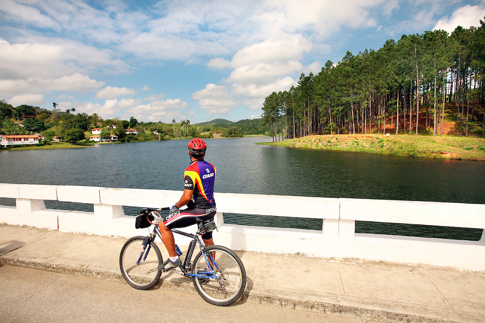 A guide points out the town and man-made lake in the Las Terrazas complex during a cycling tour of Cuba.
