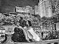 Ballerina in white tutu smelling a flower in Bryant Park at night. Dancer: Brittany Cavaco.