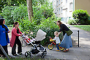 Astrid Holmann of the Hollmann Sturm family in Hamburg, Germany with her daughter Lillith Sturm as they pass two immigrant neighbors in front of their apartment. They were photographed for the Hungry Planet: What I Eat project with a week's worth of food in June. Astrid and Lillith are Model Released.