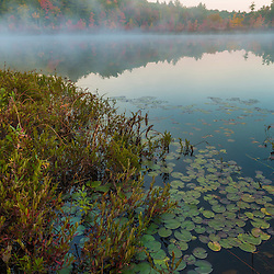 Morning mist rises from Round Pond in Barrington, New Hampshire. Fall.