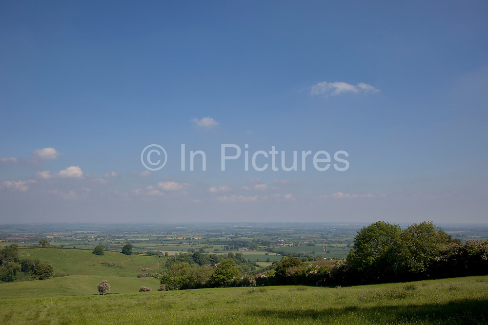View from Ilmington across Vale of Evesham. The Cotswolds, Gloucestershire, UK.  Popular with both the English themselves and international visitors from all over the world, the area is well known for gentle hillsides 'wolds', outstanding countryside, sleepy ancient limestone villages, historic market towns and for being so 'typically English' where time has stood still for over 300 years. Throughout the Cotswolds stone features in buildings and stone walls act as a common thread in seamlessly blending the historic towns & villages with their surrounding landscape. One of the most 'quintessentially English' and unspoiled regions of England.