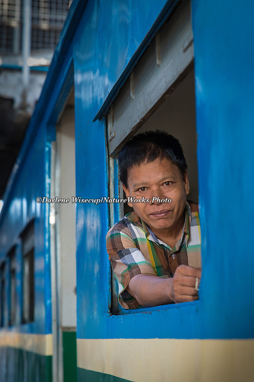 A passenger looking out the train window as he waits at the station in Yangon,  Myanmar.