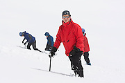 """University of Washington Climbing Club member Brian Doehle pauses while ascending a snow slope during """"Snow School"""" at Paradise in Mount Rainier National Park, Washington. At the annual club event, members practice essential skills like glacier crevasse rescue and self arrest."""