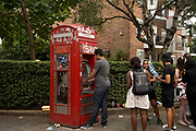 Notting Hill Carnival 2016 Childrens Day. A queue of people wait to use a cash machine in an old red telephone box.