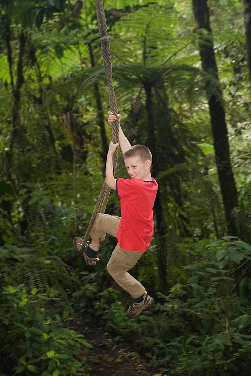 Boy (age 9) on rope swing in cloudforest, Sachatamia Lodge, Mindo, Pichincha province, Ecuador, South America.  MR