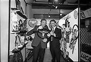 """26/06/1967<br /> 06/26/1967<br /> 26 June 1967<br /> Motoring Enthusiasts Week officially opened by Joe Lynch at the International Trade Promotion Centre, Dublin. Joe Lynch (Left) asks Mr. P. Byrne of Paddy Hopkirk Ltd. if he would care to """"Take the wheel?"""" as he examines a Safety Steering wheel on the Paddy Hopkirk Ltd. stand."""