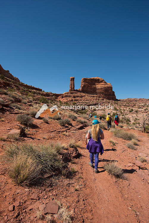 Group of moms and kids hiking Jeep Arch, Moab, Utah.