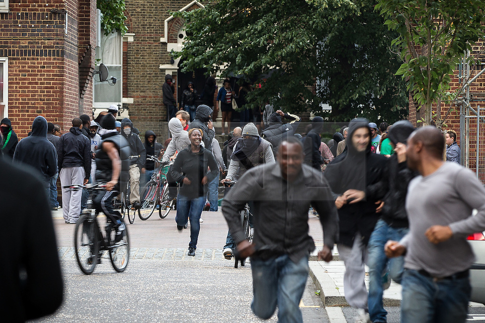 © Licensed to London News Pictures . 08/08/2011 . London , UK . People run through streets on the Pembury Estate in Hackney during a 3rd night of rioting and looting in London , which followed a protest against the police shooting of Mark Duggan in Tottenham . Photo credit : Joel Goodman/LNP