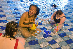 Day service users with learning disability playing in the water at a local swimming pool,