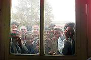 Afghan boys peer through the window of a restaurant in Taloqan, immediately after the Taliban were ousted from the city.