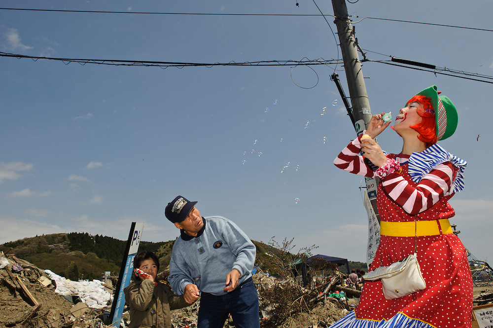 Chindonya performer Kei  Hananoya blows bubbles outside the Mangattan Manga Museum, Ishinomaki, Miyagi Prefecture, Japan, May 5, 2011. Rakugo-ka (comic story-teller) and balloon artist Diane Kichijitsu travelled with other performers to Ishinomaki to perform of victims of the March 11 earthquake and tsunami.