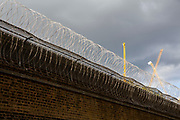 Razor wire fence attached to a large brick wall protecting the perimeter wall of HMP Pentonville, London, UK.  HM Prison Pentonville is an English Category B men's prison, operated by Her Majesty's Prison Service. Pentonville Prison is located on  Caledonian Road in the Barnsbury area of the London Borough of Islington, north London, United Kingdom. Outside the prison, yellow industrial cranes are working against a dark, grey sky. (Photo by Andy Aitchison)