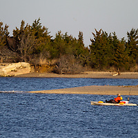 A kayaker fishing inside Horseshoe Cove at Sandy Hook.